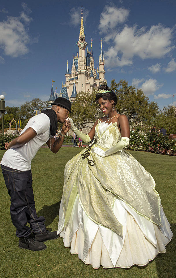 "LAKE BUENA VISTA, FL - FEBRUARY 19:  In this handout image provided by Disney Parks, singer, songwriter, composer and producer Ne-Yo (L) poses with Princess Tiana at the Magic Kingdom theme park at Walt Disney World Resort February 19, 2013 in Lake Buena Vista, Florida.  The Grammy Award-winning artist is set to embark on his international ""R.E.D. Tour,"" launching in the United Kingdom on March 4, 2013.  (Photo by Kent Phillips/Disney Parks via Getty Images)"