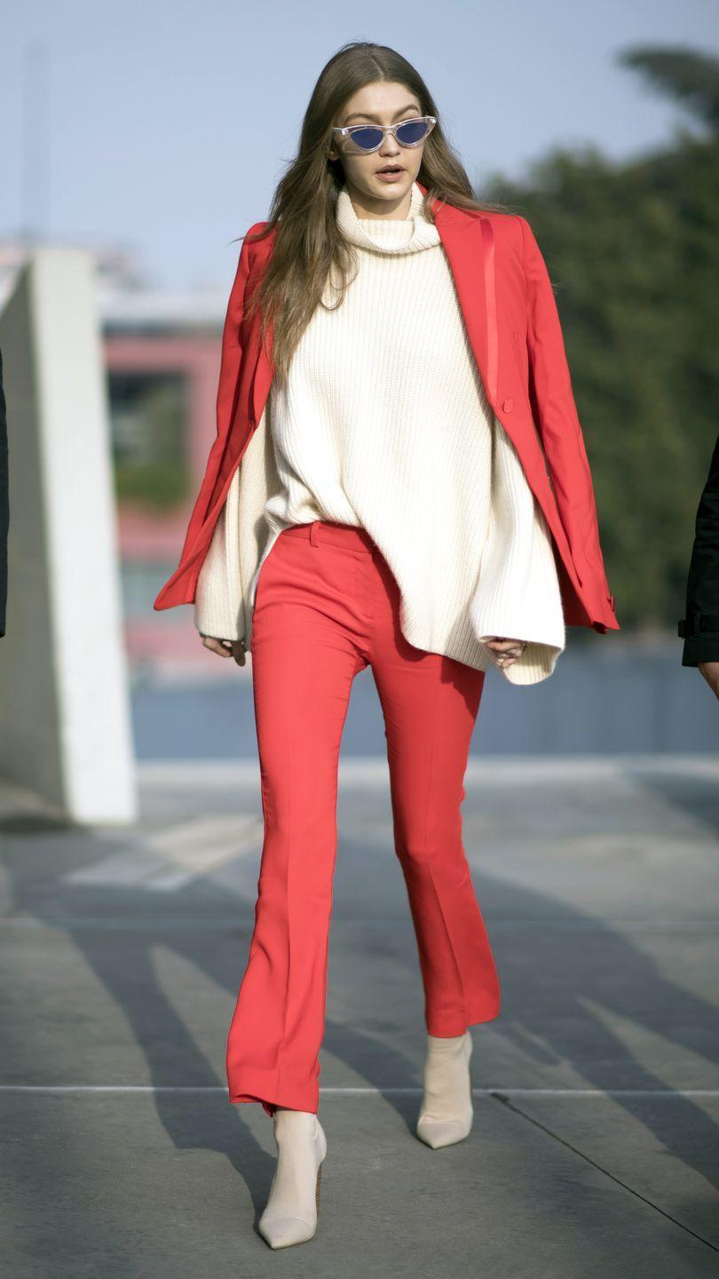 <p>The model made her way around Milan wearing a bold red Versace suit, slouchy cream-colored turtleneck and Tony Bianco ankle boots. </p>