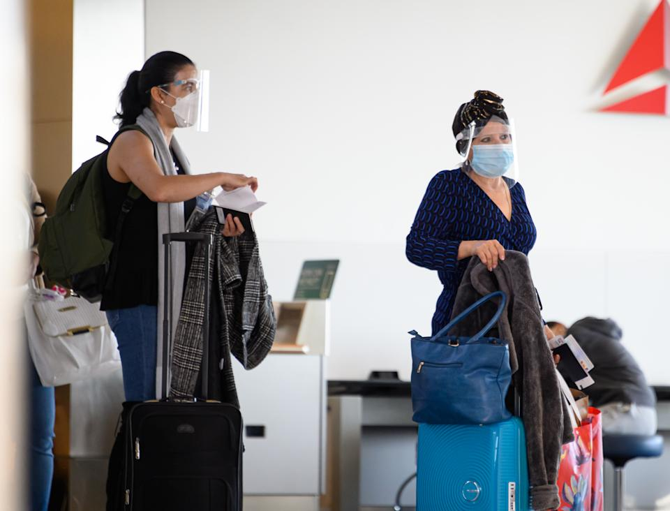 NEW YORK, NEW YORK - NOVEMBER 07: Air travelers wear face masks and face shields by a boarding gate in John F. Kennedy International Airport on November 07, 2020 in New York City. The global pandemic has had a devastating impact on aviation and airlines don't believe they will see much improvement until a reliable COVID-19 vaccine is developed and distributed.  (Photo by Noam Galai/Getty Images)