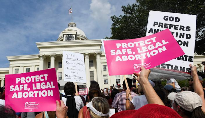 Protestors participate in a rally against one of the nation's most restrictive bans on abortion