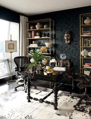 <p>Designer Richard Hallberg keeps this eclectic-chic home office from feeling over-the-top by grounding the space with black and gold. Woven faux leather walls, a textured cowhide rug, and a unique array of artifacts make this office feel like it belongs to a well-traveled owner with an impeccable eye.</p>