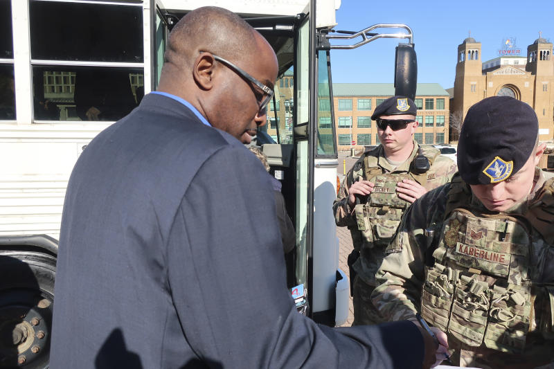 Kansas state Rep. K.C. Ohaebosim, left, D-Wichita, has his driver's license checked by military personnel before boarding a National Guard bus to a Department of Homeland Security briefing, Tuesday, Jan. 14, 2020, outside the Statehouse in Topeka, Kan. Lawmakers said the unclassified briefing dealt with potential foreign attempts to gain information about Kansas business and agricultural interests. (AP Photo/John Hanna)