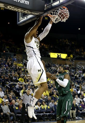Michigan forward Jordan Morgan (52) dunks as Cleveland State guard Sebastian Douglas (1) looks on during the first half of their NCAA college basketball game in the second-round of the NIT Season Tip-Off tournament at Crisler Arena in Ann Arbor, Mich., Tuesday, Nov. 13, 2012. (AP Photo/Paul Sancya)