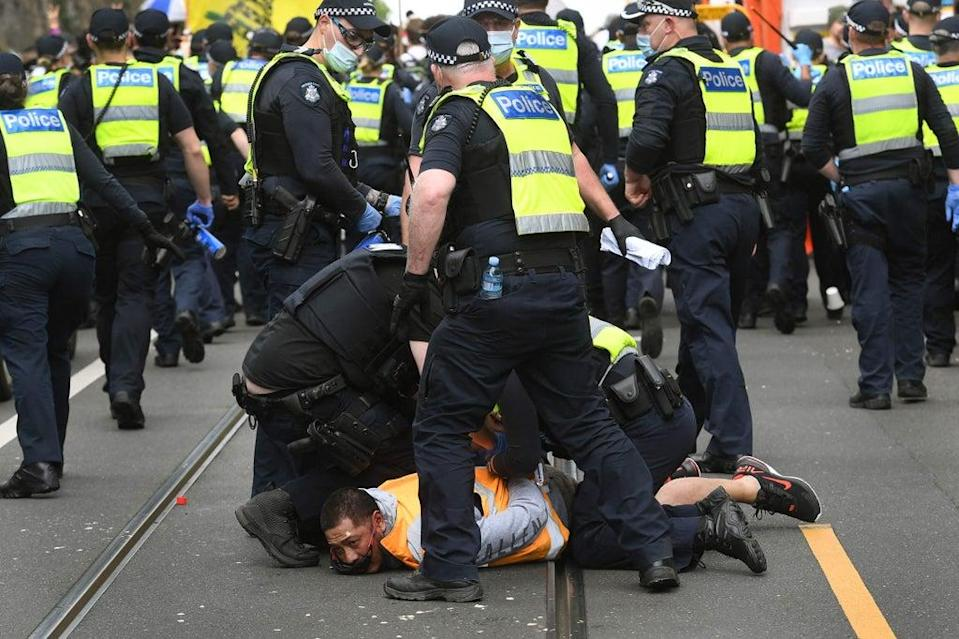 Police arrest a protester during an anti-lockdown rally in Melbourne (AFP via Getty Images)