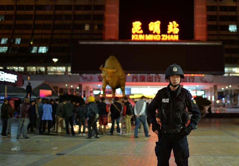 A policeman stands guard as Chinese mourners light candles at the scene of the terror attack at the Kunming train station in China's Yunnan Province on March 2, 2014 (AFP Photo/)