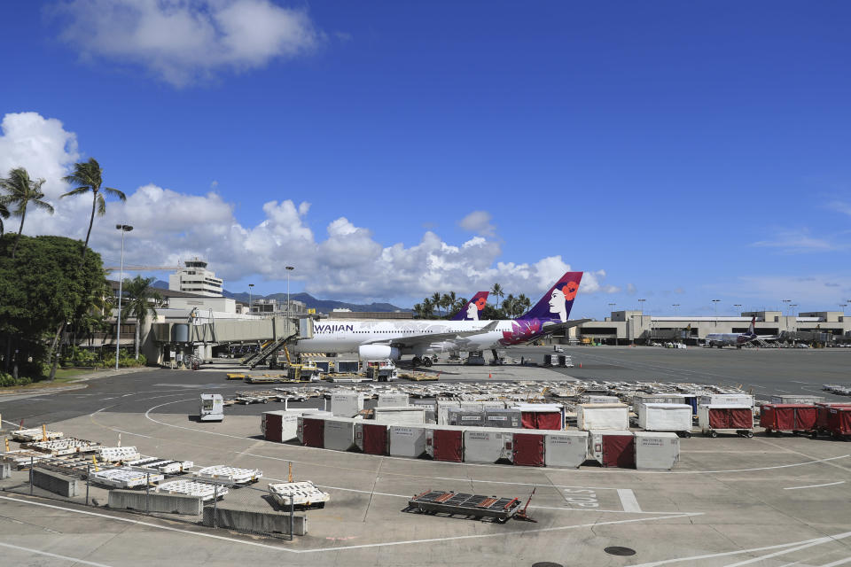 An airplane is seen parked at a terminal at the the Daniel K. Inouye International Airport Thursday, Oct. 15, 2020, in Honolulu. A new pre-travel testing program will allow visitors who test negative for COVID-19 to come to Hawaii and avoid two weeks of mandatory quarantine goes into effect Thursday. The pandemic has caused a devastating downturn on Hawaii's tourism-based economy. Coronavirus weary residents and struggling business owners in Hawaii will be watching closely as tourists begin to return to the islands. (AP Photo/Marco Garcia)