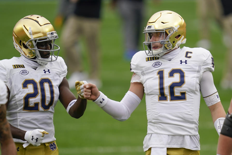 Notre Dame quarterback Ian Book (12) greets running back C'Bo Flemister (20) during warmup before an NCAA college football game against Pittsburgh, Saturday, Oct. 24, 2020, in Pittsburgh. (AP Photo/Keith Srakocic)