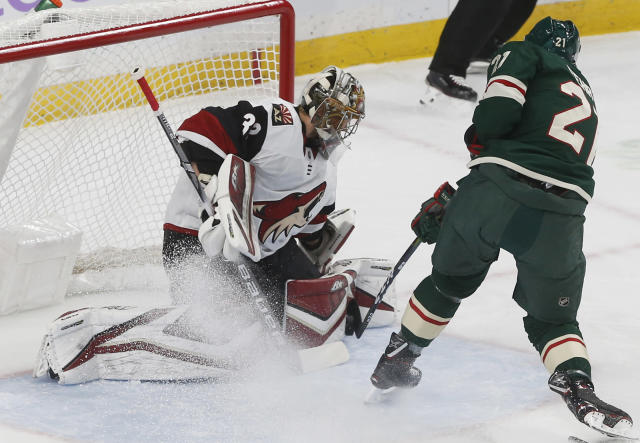 Arizona Coyotes goalie Antti Raanta, left, of Finland, stops a shot by Minnesota Wild's Eric Fehr during the first period of an NHL hockey game Tuesday, Nov. 27, 2018, in St. Paul, Minn. (AP Photo/Jim Mone)
