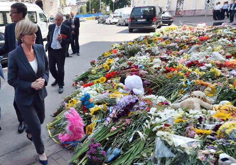 Australian Foreign Minister Julie Bishop walks past flowers laid in memory of the victims of downed Malaysia Airlines flight MH17 outside the Netherlands' embassy in Kiev on July 24, 2014 (AFP Photo/Sergei Supinsky)