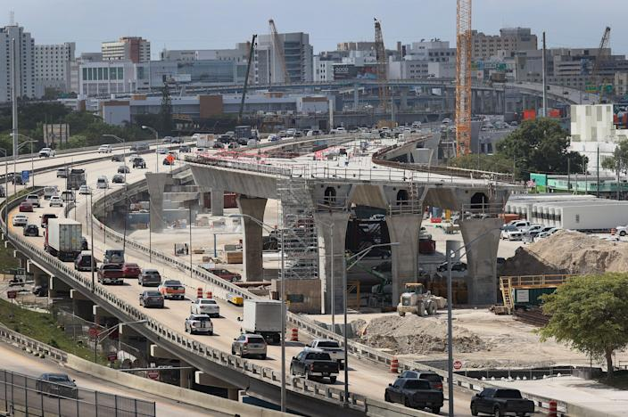 """MIAMI, FLORIDA - MARCH 17: Construction workers build the """"Signature Bridge,"""" replacing and improving a busy highway intersection at I-95 and I-395 on March 17, 2021 in Miami, Florida. The Florida Department of Transportation is building the project in partnership with the Miami-Dade Expressway Authority and its contractor, the Archer Western-de Moya Group Joint Venture. The infrastructure project will ease traffic congestion, connect communities with downtown neighborhoods, and provide an iconic bridge for Miami's skyline. The entire project is scheduled for completion in the fall of 2024 at the cost of $818 million. (Photo by Joe Raedle/Getty Images)"""