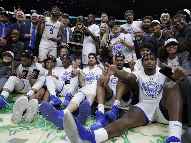 Buffalo team members celebrate with the trophy after defeating Bowling Green 87-73 in an NCAA college basketball game for the Mid-American Conference men's tournament title Saturday, March 16, 2019, in Cleveland. (AP Photo/Tony Dejak)