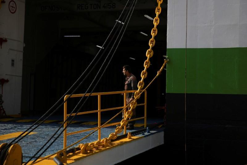 A seaman stands at the entrance of a moored passenger ferry during a 24-hour general strike at the port of Piraeus
