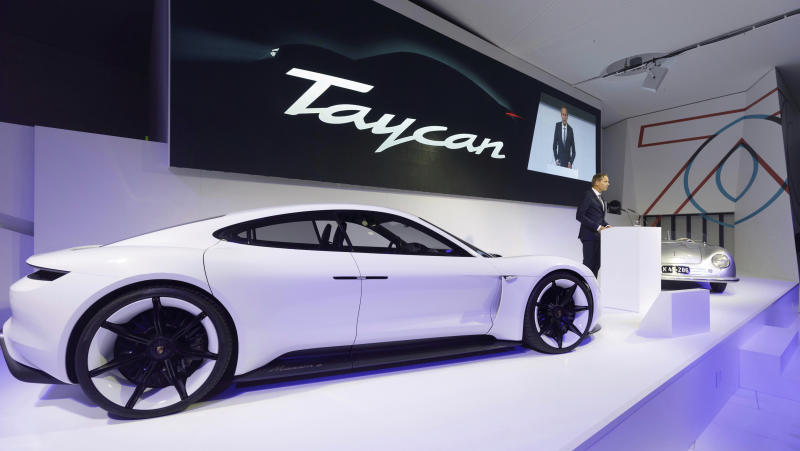 """In this Aug. 6, 2018, photo provided by Porsche AG, Oliver Blume, CEO of Porsche AG, speaks next to the Taycan during the ceremonial opening of """"70 Years Porsche Sportscar"""" at the Porsche Museum in Stuttgart, Germany. While Tesla grapples with internal issues like production delays, a sometimes-erratic CEO and a recent about-face on whether to go private, its rivals are moving aggressively into the luxury electric vehicle space. Porsche is taking on Tesla's Model S high performance luxury car with the Taycan, expected to reach the market in late 2019. (Porsche AG via AP)"""