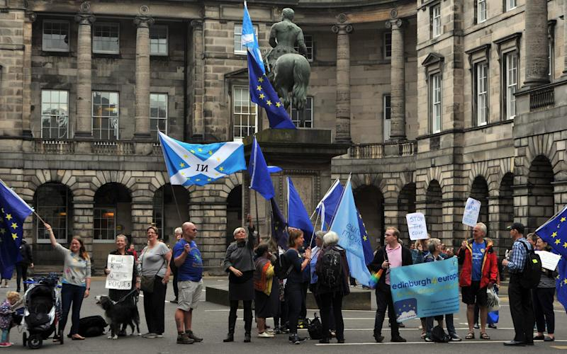 Activists hold EU and Scottish Saltire flags as they demonstrate outside of the Court of Session in Edinburgh last week - AFP