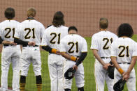 Pittsburgh Pirates, all wearing Roberto Clemente's No. 21 for Roberto Clemente Day, watch a tribute to the Pirates Hall of Fame right fielder before the team's baseball game against the Chicago White Sox in Pittsburgh, Wednesday, Sept. 9, 2020. (AP Photo/Gene J. Puskar)