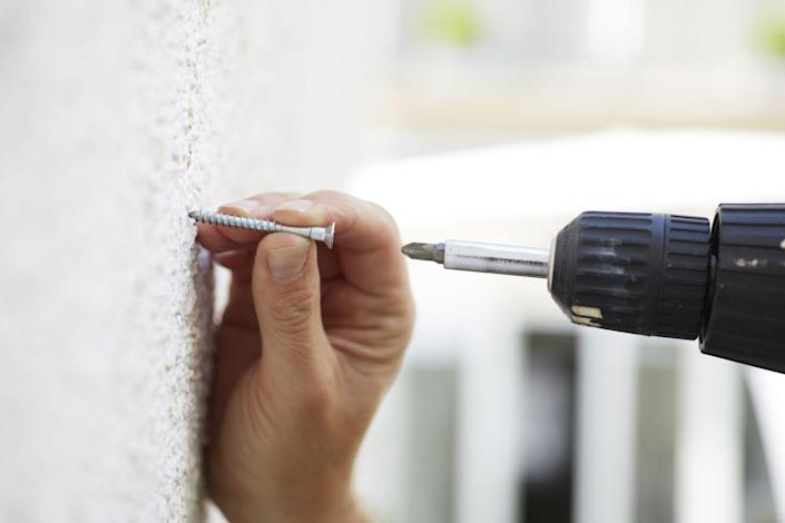 """<p><strong>Step 1: Determine your surface.</strong> Most houses will have drywall, but many built before 1950 used lath and plaster, which is harder than drywall, brittle, and much thicker. You can feel the difference, but if you're still not sure, a pushpin will go into drywall. It won't go into plaster.</p><p><strong>Step 2: Find the studs. </strong>Whether you're hanging a kitchen cabinet or a coat hook, your best option is to<a href=""""https://www.popularmechanics.com/home/a28842874/best-stud-finders/"""" rel=""""nofollow noopener"""" target=""""_blank"""" data-ylk=""""slk:attach things to a stud"""" class=""""link rapid-noclick-resp""""> attach things to a stud</a>. If you're working with plaster, this can be tough, since the fasteners used to attach the lath will throw off a stud finder. One way to cheat is to look for a light switch. Most are mounted inside the first stud by the door frame. (The box holding its wiring needs to be attached to something sturdy.) </p><p>Take off the switch plate and you can see which side of the stud the box is mounted on by spotting the screws. Most wall framings set studs every 16 inches, so you should be okay to measure from there, but double-check with a pilot hole. You <a href=""""https://www.popularmechanics.com/about/a27923491/best-cordless-drills/"""" rel=""""nofollow noopener"""" target=""""_blank"""" data-ylk=""""slk:need to drill"""" class=""""link rapid-noclick-resp"""">need to drill</a> through the plaster and into the wood framing. <a href=""""https://www.popularmechanics.com/home/tools/g23341902/best-drill-bit-sets/"""" rel=""""nofollow noopener"""" target=""""_blank"""" data-ylk=""""slk:Expect your bit"""" class=""""link rapid-noclick-resp"""">Expect your bit</a> to take a beating from the harder material. While most drywall is 3/8 or 1/2 inch thick—and thus works with 1 1/4-inch screws for light loads—plaster can range from 3/4 inch to 1 1/4 inches thick, so you may need screws up to 2 1/2 inches long.</p><p>If you're working with drywall, you have a few more options:</p><p>Scan the wall with a stud"""