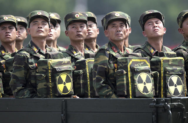 <p>North Korean soldiers turn and look towards their leader Kim Jong Un from a military parade vehicle as they carry packs marked with the nuclear symbol during a ceremony marking the 60th anniversary of the Korean War armistice in Pyongyang, North Korea, July 27, 2013. (Wong Maye-E/AP) </p>