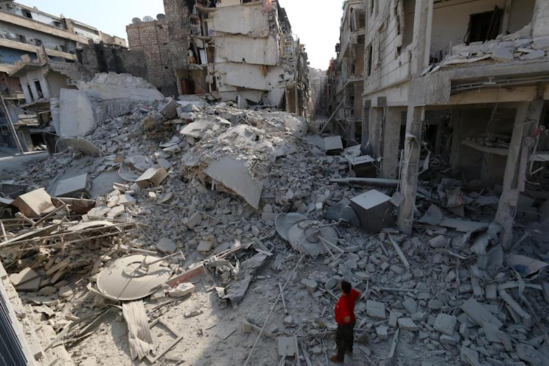 A Syrian man looks at the rubble of a five story apartment building that was destroyed in a barrel bomb attack in Aleppo on August 27, 2014
