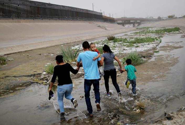 Migrants hold hands as they cross the border between the U.S. and Mexico at the Rio Grande river, on their way to enter El Paso, Texas, on May 20, 2019 as taken from Ciudad Juarez, Mexico. The location is in an area where migrants frequently turn themselves in and ask for asylum in the U.S. after crossing the border. Approximately 1,000 migrants per day are being released by authorities in the El Paso sector of the U.S.-Mexico border amidst a surge in asylum seekers arriving at the Southern border.