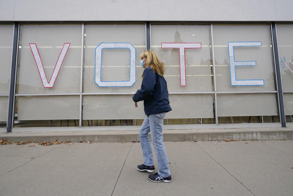 A local resident arrives to cast her ballot during early voting for the general election, Tuesday, Oct. 20, 2020, in Adel, Iowa. (AP Photo/Charlie Neibergall)