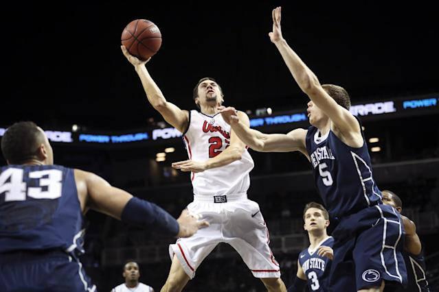 Mississippi guard Marshall Henderson (22) shoots over Penn State forward Donovon Jack (5) as forward Ross Travis (43) and guard Graham Woodward (3) stand by in the first half of an NCAA college basketball game, the championship game of the Barclays Center Classic, Saturday, Nov. 30, 2013, in New York. (AP Photo/John Minchillo)