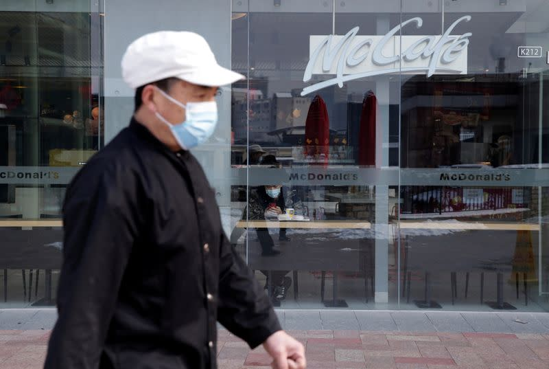 FILE PHOTO: Man wearing a face mask walks past a McDonald's store at a shopping area in Beijing