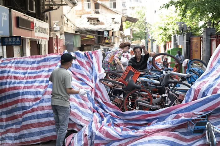 """A makeshift barricade of rental bikes and plastic tarpaulin blocks a road in Wuhan, China. Roadblocks had been part of the lockdown and had finally been removed when the restrictions ended. <span class=""""copyright"""">(For The Times)</span>"""