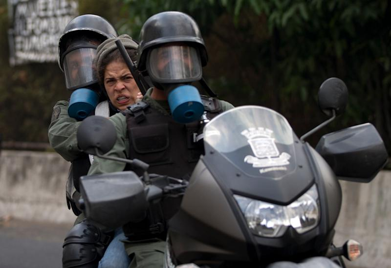 A demonstrator is taken away on a motorcycle by Bolivarian National Guards soldiers during clashes at an anti-government protest in Caracas, Venezuela, Saturday, April 26, 2014. Student organizers at the last minute decided against marching downtown to avoid a confrontation with security forces in the government-controlled district. Instead they concentrated in the wealthier, eastern neighborhoods that have been the hotbed of unrest since February. (AP Photo/Fernando Llano)