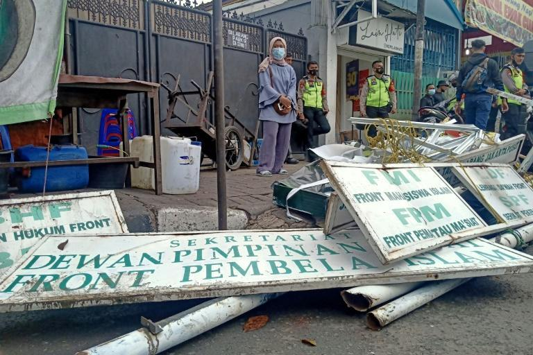 Police tore down signs at the headquarters of Indonesian hardline Islamic Defenders Front after banning the organisation