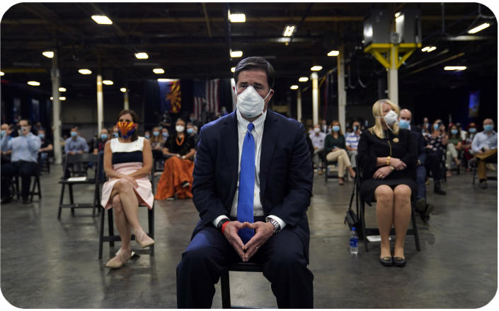 Arizona Gov. Doug Ducey waits to hear President Donald Trump speak at a Honeywell plant manufacturing personal protective equipment in Phoenix.