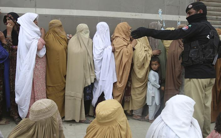 """Women wait in line to receive cash under a government relief program in Peshawar, Pakistan, in April. <span class=""""copyright"""">(Muhammad Sajjad / Associated Press)</span>"""