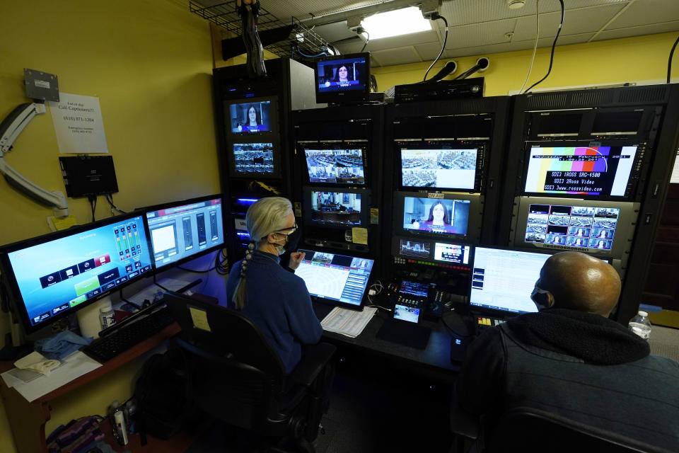 Virginia Public Media techs, Roberta Fallon, left, and Phillip Newsome, right, monitor the video feeds during a Virginia House of Delegates Zoom Legislative session at the Capitol in Richmond, Va., Wednesday, Feb. 10, 2021. (AP Photo/Steve Helber)