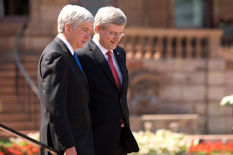 Prime Minister Stephen Harper right, and Michigan Governor Rick Snyder walk in front of the original Hiram Walker and Sons estate on the banks of the Detroit River in Windsor, Ontario, Canada, on Friday, June 15, 2012, ahead of an announcement for a new $1-billion bridge connecting the city with Detroit. (AP Photo/The Canadian Press,Mark Spowart )