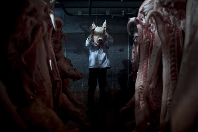 <p>An employee of the Mizra pork factory poses with a pig's head in a refrigerated warehouse in Kibbutz Mizra, northern Israel, on Dec. 6, 2012. The million-strong Soviet immigrant community has increased customer demand for pork in the country, a non-kosher food rarely eaten by Israeli Jews. (Photo: Oded Balilty/AP) </p>