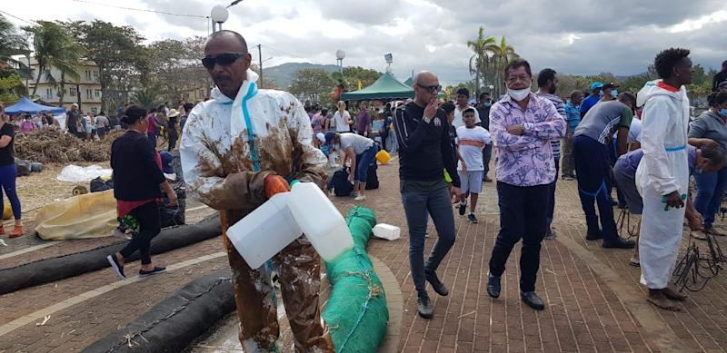 A street in Mauritius. A man in a biohazard suit and sunglasses holds plastic bottles. He is covered in oil.