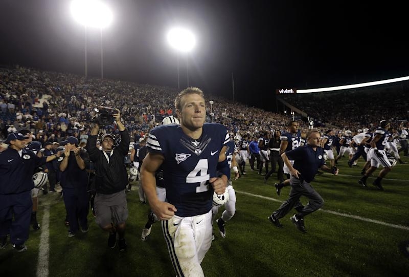 Brigham Young quarterback Taysom Hill (4) leaves the field following their NCAA college football game against Texas on Saturday, Sept. 7, 2013, in Provo, Utah. BYU defeated Texas 40-21. (AP Photo/Rick Bowmer)