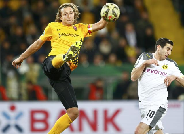 Dynamo Dresden's Michael Hefele (L) and Borussia Dortmund's Henrikh Mkhitaryan go for the ball during their German Cup (DFB Pokal) soccer match in Dresden March 3, 2015. REUTERS/Hannibal Hanschke (GERMANY - Tags: SOCCER SPORT) DFB RULES PROHIBIT USE IN MMS SERVICES VIA HANDHELD DEVICES UNTIL TWO HOURS AFTER A MATCH AND ANY USAGE ON INTERNET OR ONLINE MEDIA SIMULATING VIDEO FOOTAGE DURING THE MATCH.