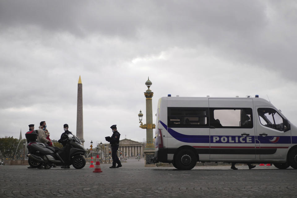 Police officers control a scooter in Paris, Friday, Oct. 30, 2020. France re-imposed a monthlong nationwide lockdown Friday aimed at slowing the spread of the virus, closing all non-essential business and forbidding people from going beyond one kilometer from their homes except to go to school or a few other essential reasons. (AP Photo/Thibault Camus)