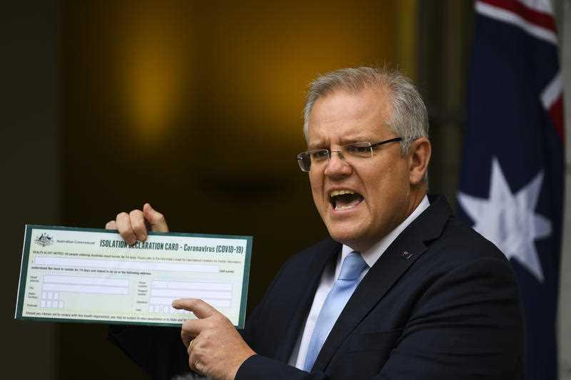 Australian Prime Minister Scott Morrison holds up a Coronavirus Isolation Declaration Card as he speaks to the media during a press conference at Parliament House in Canberra.