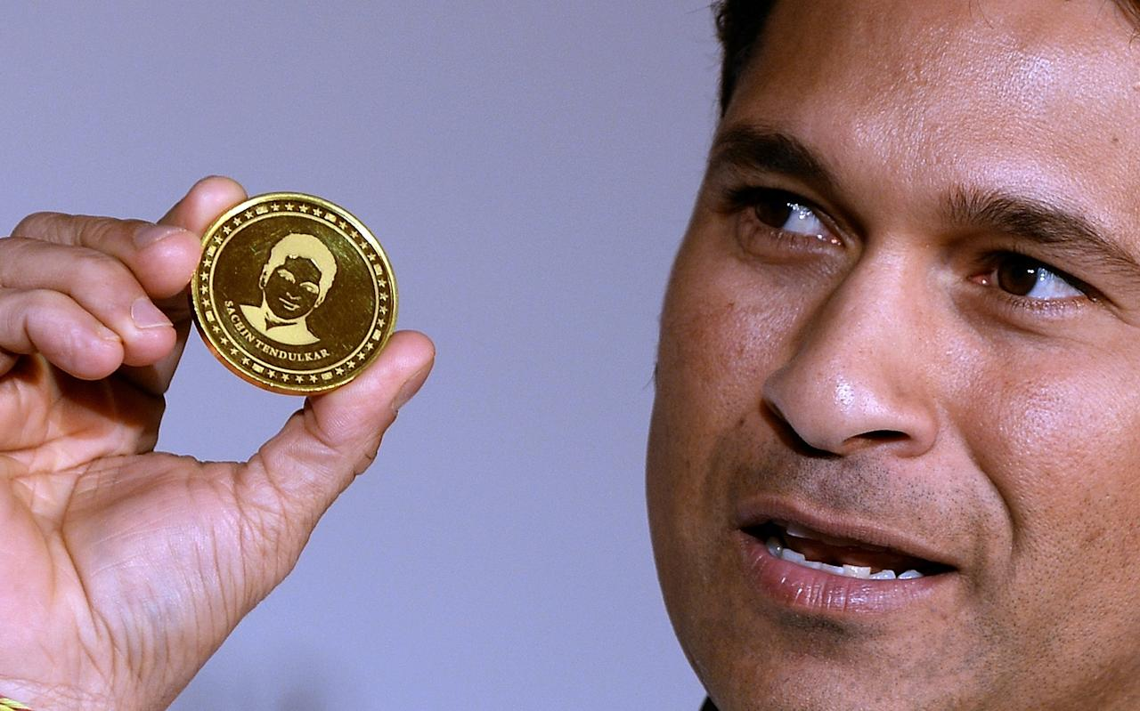 Indian cricketer Sachin Tendulkar displays a limited edition 10 gram gold coin with an embossed image of himself after unveiling it on Akshaya Tritiya in Mumbai on May 13, 2013. A total of 100, 000 limited edition 10 gram Tendulkar Gold coins priced at INR 34,000 (USD 618) will be available for both online purchase and at retail stores of leading jewellers across the country. Akshaya Tritiya is considered to be an auspicious day in the Hindu calendar to buy valuables and people generally flock to buy gold on this day in the belief that it will increase their wealth.   AFP PHOTO/ Indranil MUKHERJEE