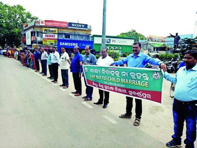 """Activists form a human chain with a banner """"Say No To Child Marriage"""" in Sonepur, Odisha"""