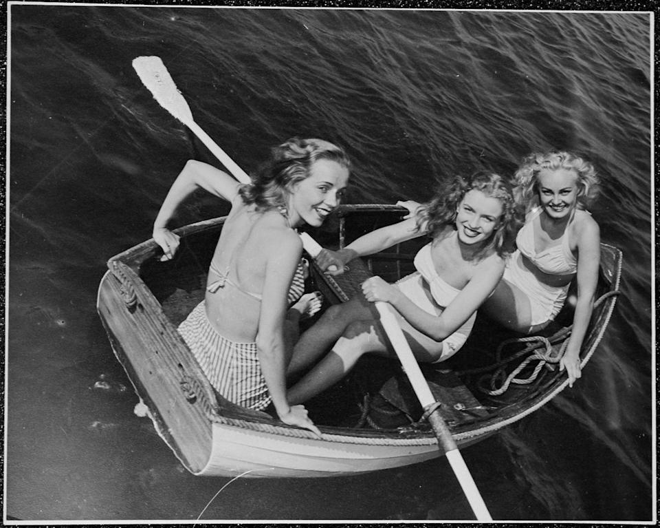 <p>Future film star Marilyn Monroe, then known as Norma Jeane Baker, out rowing with a two friends, circa 1941. </p>