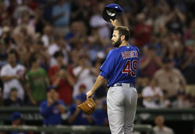 Chicago Cubs starting pitcher Jake Arrieta tips his cap as he gets a standing ovation from Red Sox's fans after carrying a no-hitter to the eighth inning of a baseball game at Fenway Park in Boston, Monday, June 30, 2014. Boston Red Sox's Stephen Drew broke up his bid with a single in the eighth inning. (AP Photo/Charles Krupa)