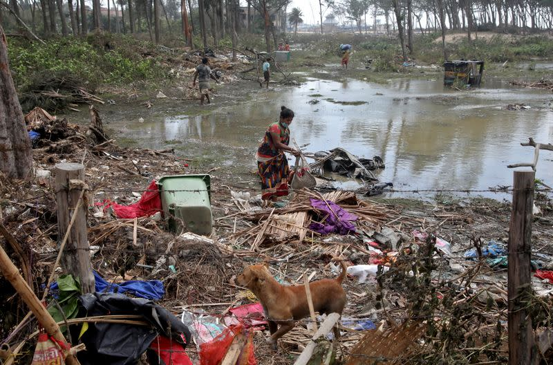FILE PHOTO: A woman salvages her belongings near her damaged hut following Cyclone Yaas in Digha