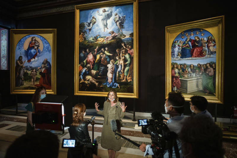 Vatican Museums Barbara Jatta speaks to the media as she stands in front of Raphael's oil on canvas altarpieces, from left, the Madonna of Foligno, the Transfiguration, and the Incarnation of the virgin, at the Vatican Museums, Wednesday, May 3, 2020.The Vatican Museums announced last month that after restorations they have determined that two of the female figures in the Hall of Constantine were oil painted by Raphael himself and not by his worship. (AP Photo/Domenico Stinellis)