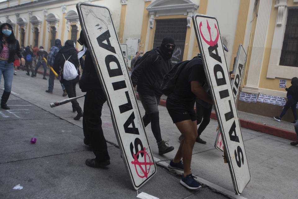 Demonstrators use transits signs as shields in front of the Congress building after protesters set a part of the building on fire, in Guatemala City, Saturday, Nov. 21, 2020. Hundreds of protesters were protesting in various parts of the country Saturday against Guatemalan President Alejandro Giammattei and members of Congress for the approval of the 2021 budget that reduced funds for education, health and the fight for human rights. (AP Photo/Oliver De Ros)