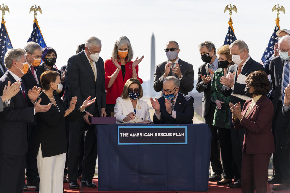 Nancy Pelosi and Chuck Schumer, seated at a small table outdoors with the Washington Monument visible in the background and surrounded by others and American flags, celebrate after signing the $1.9 trillion COVID-19 relief bill