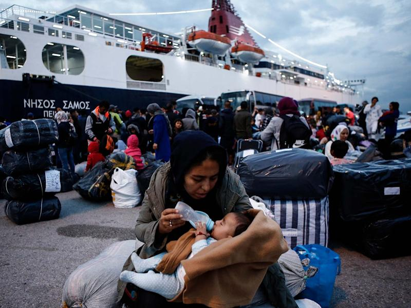 A woman feeds her baby after disembarking from the ferry Nissos Samos upon her arrival from Lesvos island to the Greek port of Piraeus: EPA