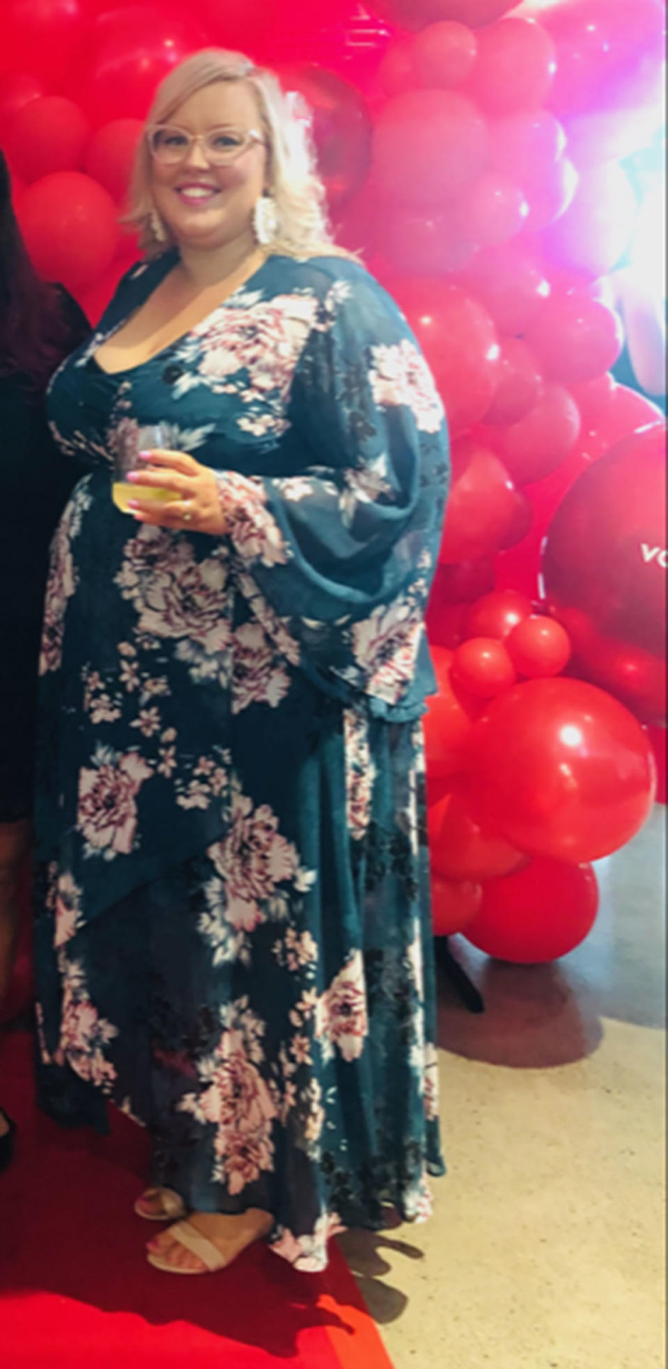 A woman wearing a long floral print dress in front of red balloons
