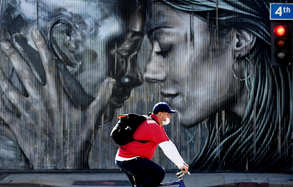 A man rides his bike along 4th Street in Los Angeles with a mural of two people behind him.